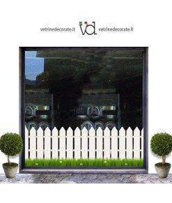vetrina decorata con una porzione di una staccionata bianca con prato primaverile fiorito