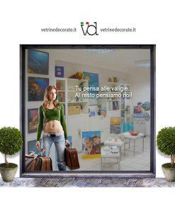 vetrina con giovane-turista-con-due-valigie