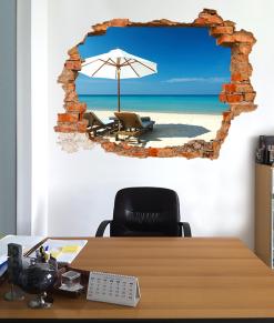 finto buco su parete dell'ufficio con dietro una spiaggia con sdraio ed ombrellone